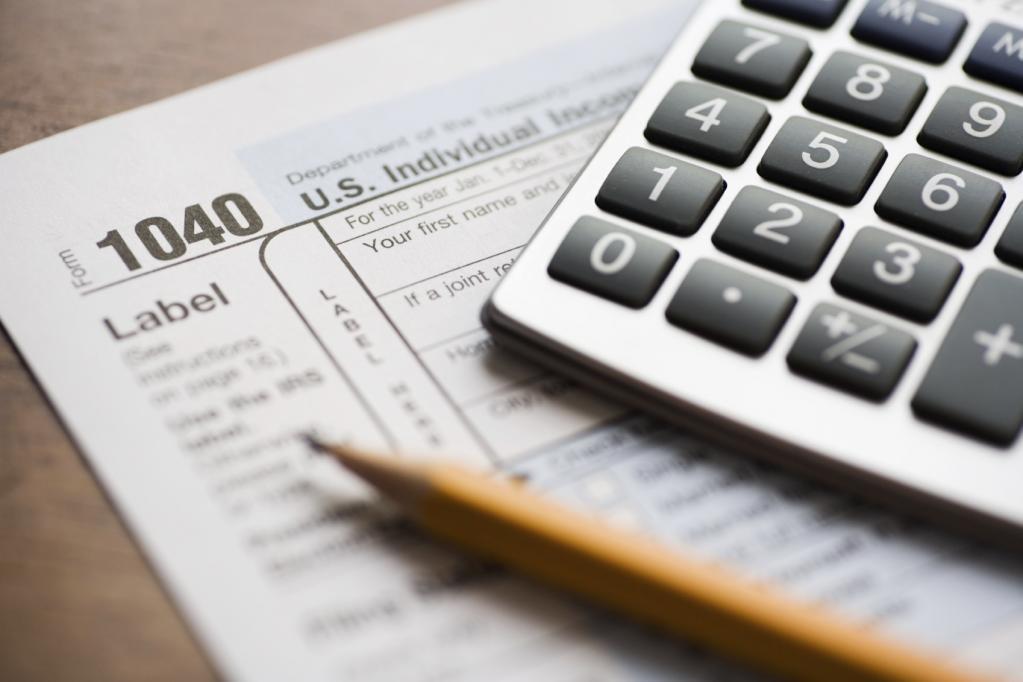 Калькулятор и карандаш на листе бумаги.