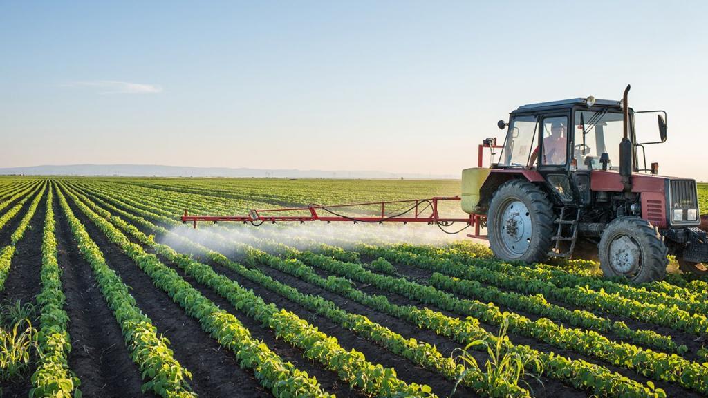 трактор поливает растения