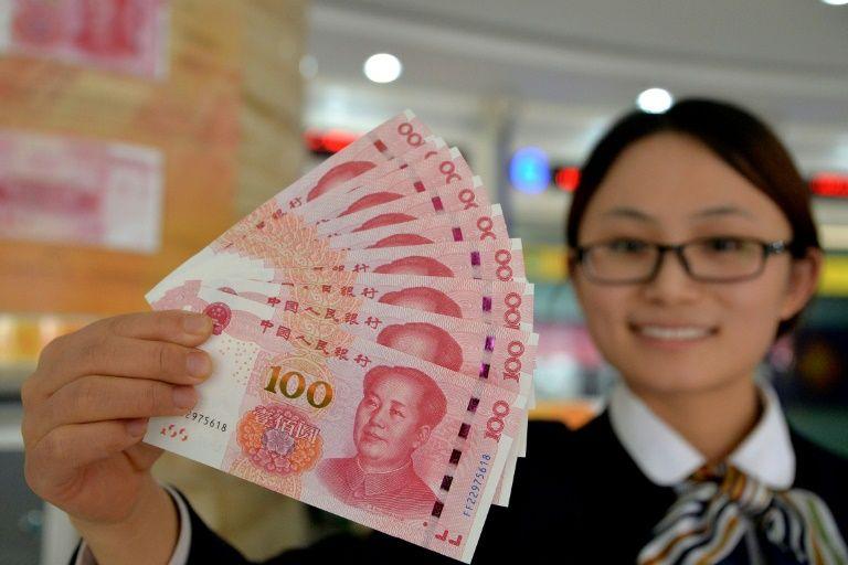 Девушка держит в руках новенькие юани.