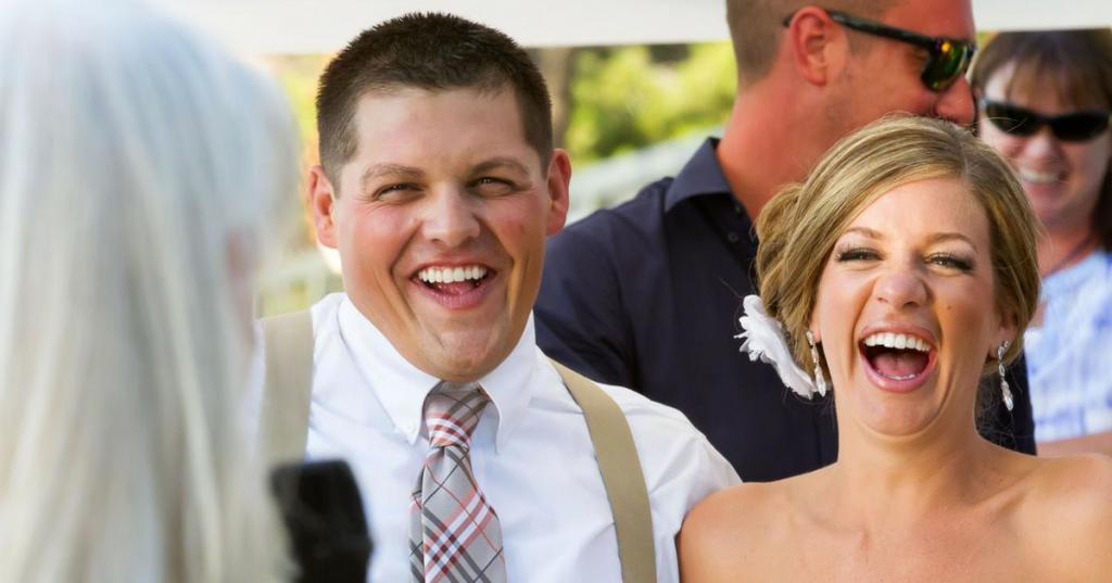 Парень и девушка смеются на фото.