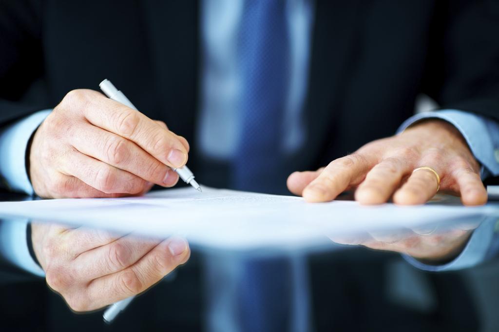 Человек подписывает документ